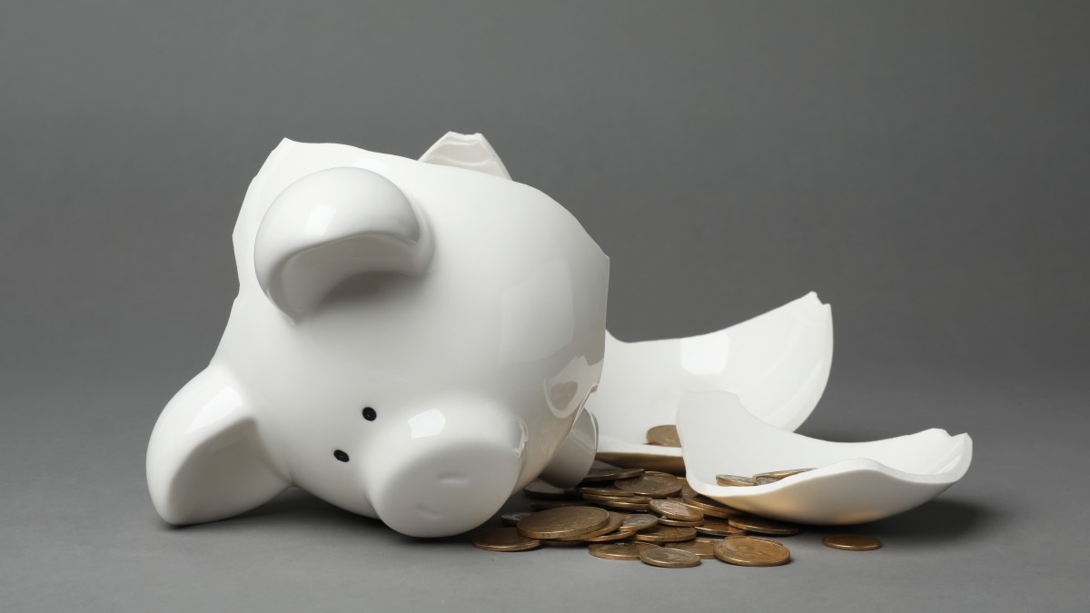 Stop throwing money at your business problems, by Lisa Larter / Broken piggy bank with coins on gray background