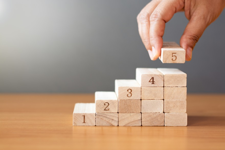 5 Growth Strategies for next year, by Lisa Larter. Women hand putting a wooden block on top and arranging wooden blocks stacking on wooden table in the shape of a staircase, Business concept for growth success process.
