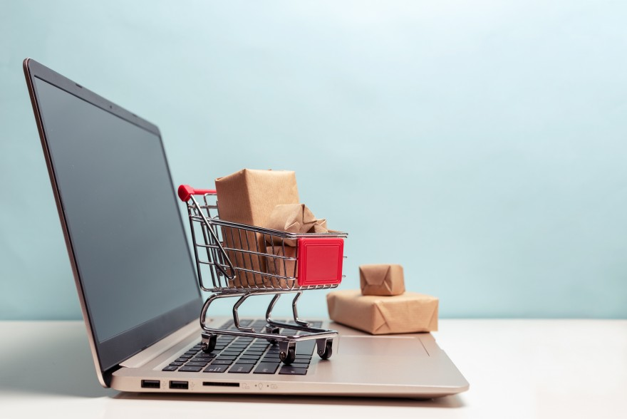 Tiny shopping cart filled with brown packages, on top of laptop. The Lifetime Value of a Client - Lisa Larter