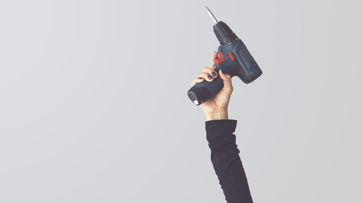 Hand raised up holding drill screwdriver