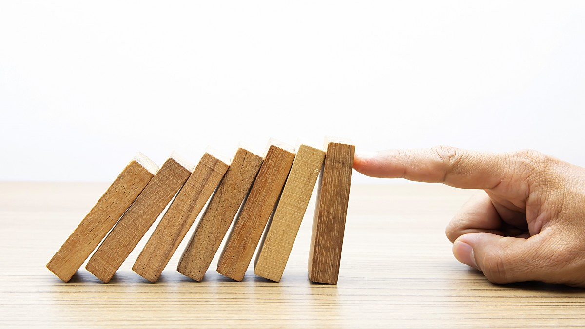 Businessman hand stoped wooden domino effect for risk management and insurance concept.