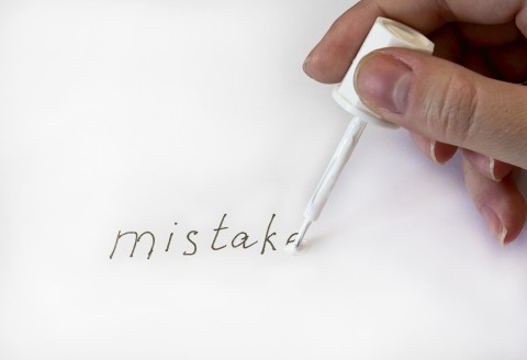 The word mistake written on paper and a persons hand using white-out to erase it