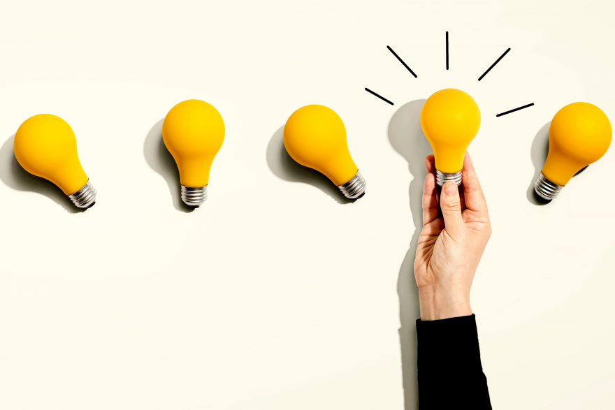 White background with 6 yellow light bulbs. Woman's hand holding one illuminated one.