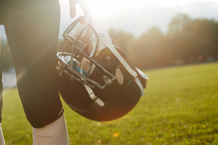 Woman American football player holding helmet on a background of dawn.