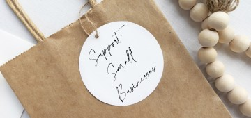 "Brown paper gift bag with a tag that reads, ""support small businesses"""