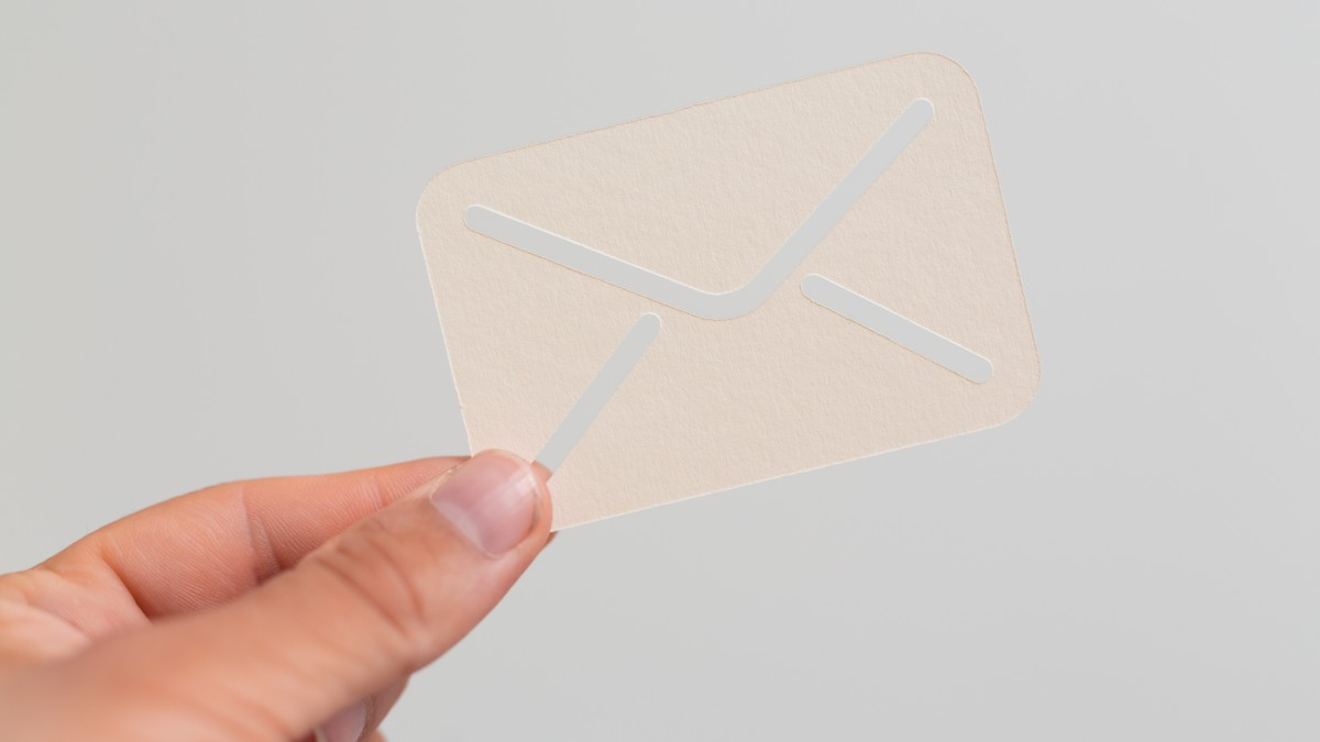 Hand holding small paper envelope email symbol