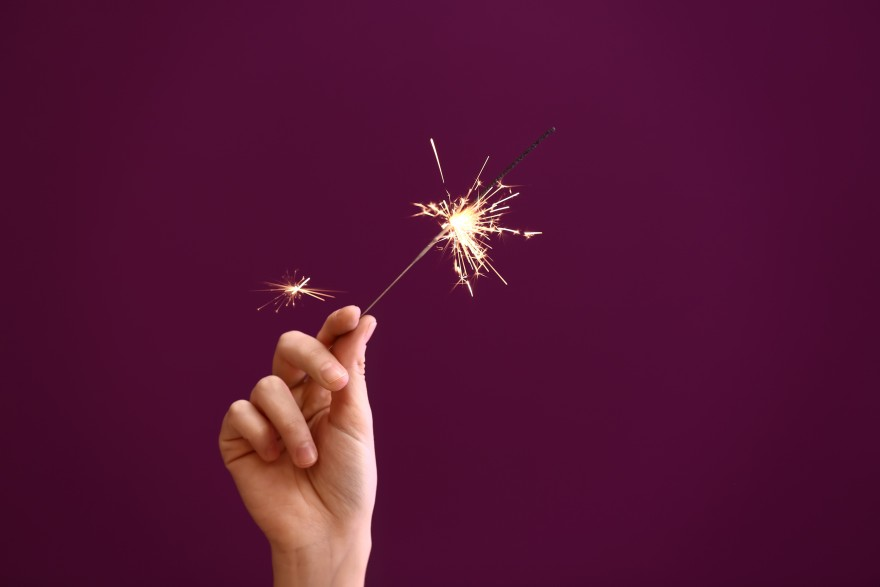 Woman holding Christmas sparkler on color background