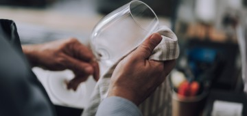 Man wiping wine glass with special rag - Second Chances
