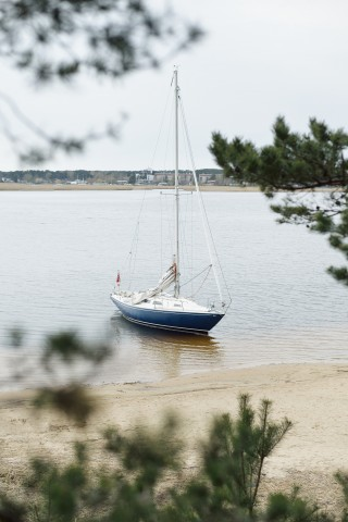 Blue sloop rigged yacht anchored in the shallow water near the sandy beach. Lule river, Sweden. Aerial view from the evergreen forest. Travel destinations, sport, amateur recreational sailing