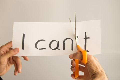 "Hands cutting the ""t"" off a piece of paper that says ""can't"""