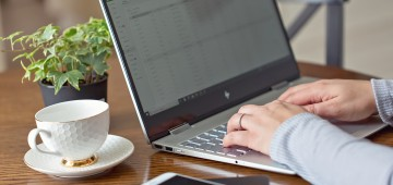 Image of a womans hands typing on a black laptop with a cup of coffee next to her