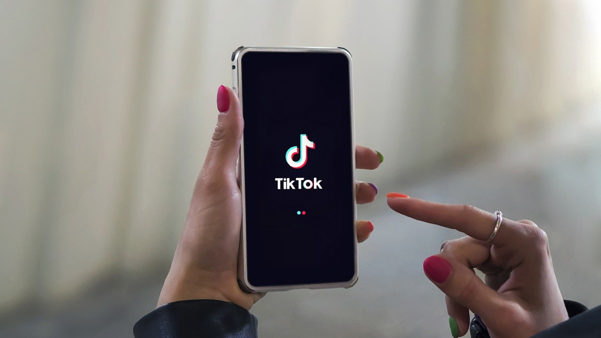 Women holding Phone with TikTok logo on the screen. Tik Tok is app to create and share videos