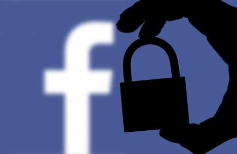 Facebook security issues. Silhouette of a hand holding a padlock infront of the facebook logo