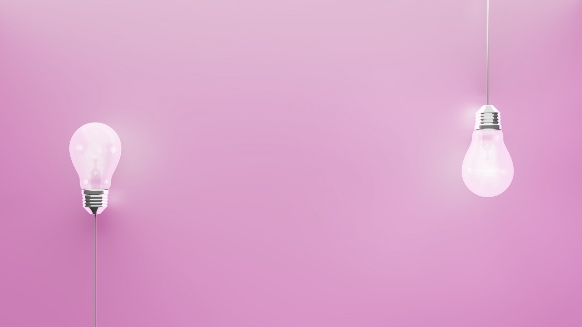 Two pink light bulbs on pink background with space for text