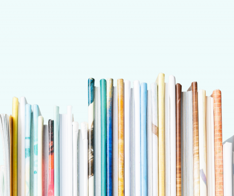 Close view of Stack of children's books on a pastel blue background. Long wide banner with copy space.