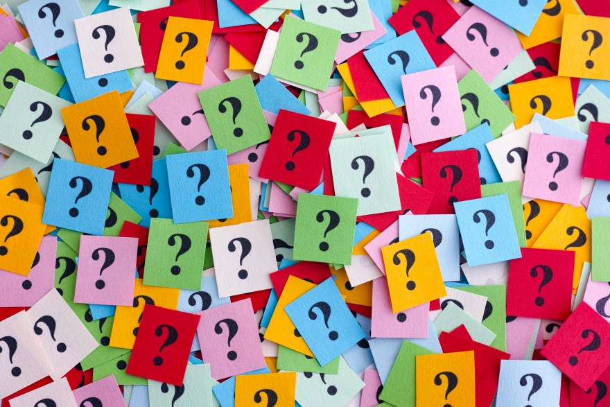 Pile of colourful paper notes with question marks.