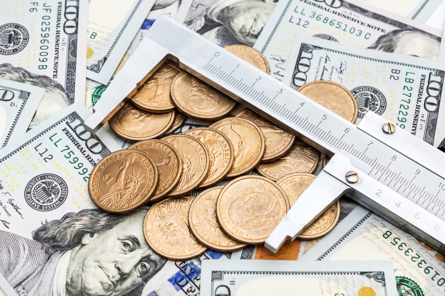 Vernier caliper with coins on background of dollar bills. Business concept.
